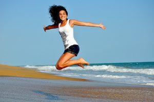 Chica saltando alegre en playa